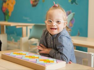 Copy-of-Child-with-Down-syndrome-in-classroom-looking-to-camera-e1569526400120-300x225.jpg
