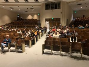 Workshop attendees wave to the camera in the workshop auditorium
