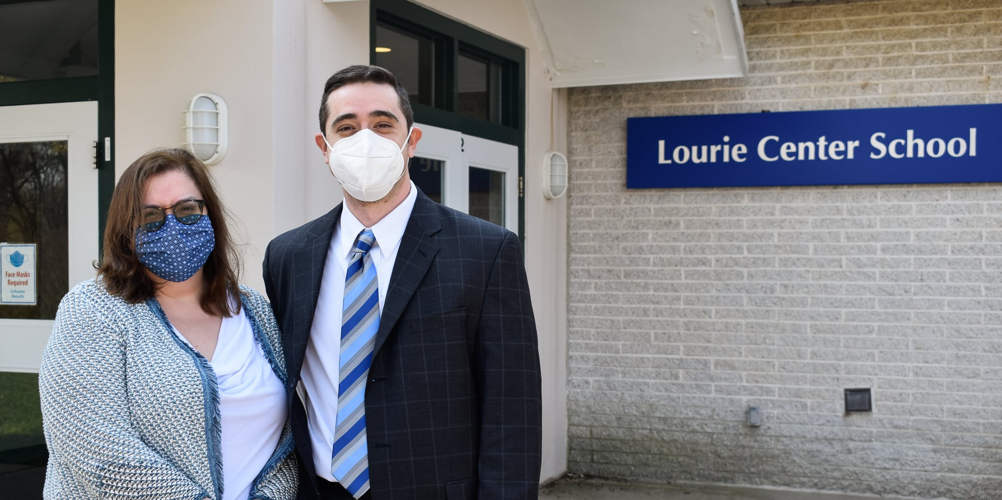 Two professionals stand outside the Lourie Center